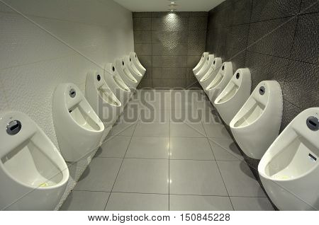 Many indoor urinals men in a public toilet.