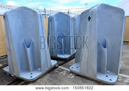 Many public portable outdoor men urinal units.