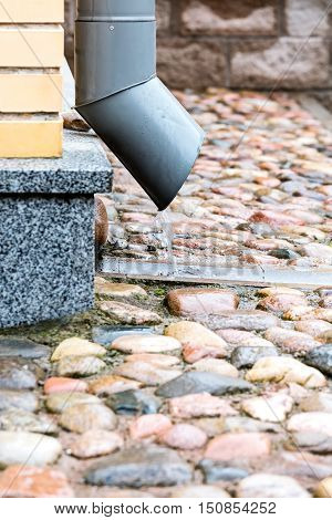 Rain Water Pouring Out From Metal Downspout On Stone Pavement