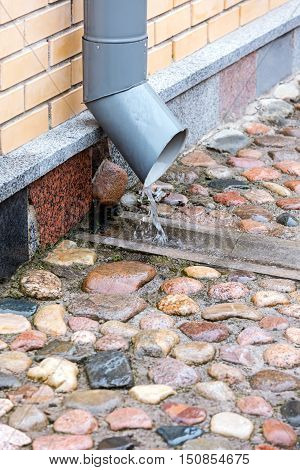 Metal Downspout On Brick Building With Water Flowing From It