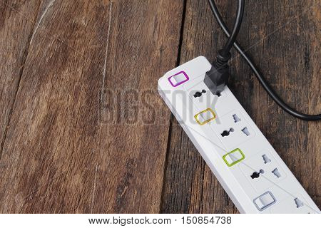 Electric white socket power bar or extension block and one plugged in power cord on wooden table background Top view and copy space
