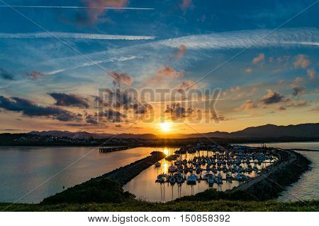 Sunset landscape of coastal city with dramatic clouds and plane trails on the background. Muttonbird Island Nature Reserve Coffs Harbour Australia