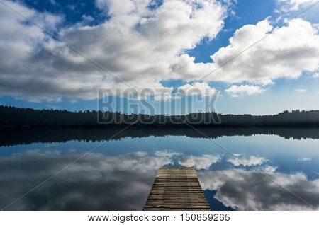 Lake Ianthe with wooden jetty on calm sunny day. Nature landscape. Perfect water reflection of quite water with wharf. South Island New Zealand