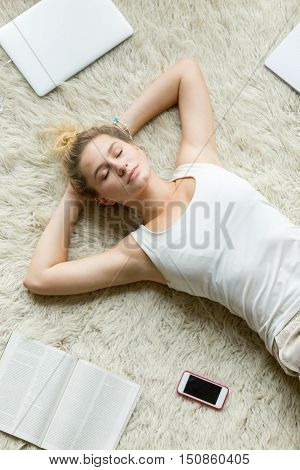 Beautiful young woman holding hands behind head while lying on white carpet on the floor in living room and sleeping after working on laptop or studying at home. Top view close-up image