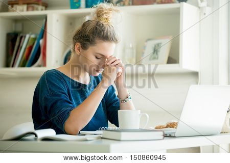 Portrait of an attractive woman at table with cup and laptop, book, notebook on it, praying position. Bookshelf at the background, concept photo