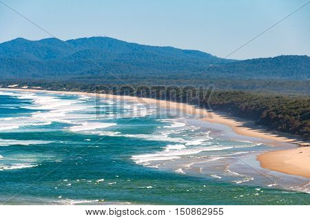 Aerial view of Australian coastal sand beach with mountains on the background. Nambucca Heads NSW Australia
