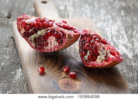 Pomegranate with arils on a  brown cutting board on a light background