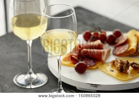 Glasses with white wine and tasty snacks on a table