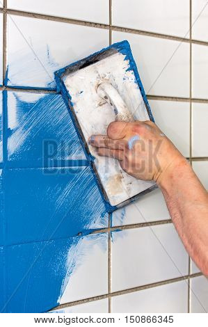 Workman Applying Blue Grout To White Tiles
