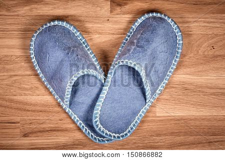 Blue Home Slippers On A Brown Wooden Floor