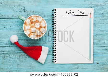 Cup of hot cocoa or chocolate with marshmallow Santa Claus hat and notebook with wish list on turquoise vintage table from above, christmas planning concept. Flat lay style.