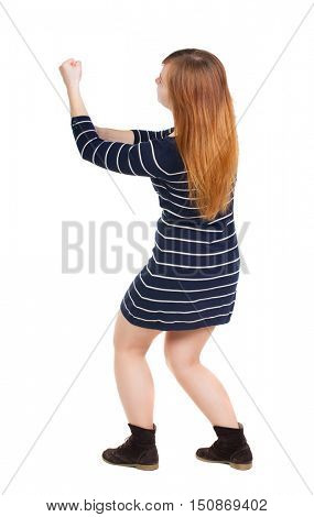 back view of standing woman pulling a rope from the top or cling to something.  Rear view people collection.  backside view of person.  Isolated over white background. girl in a dark blue dress