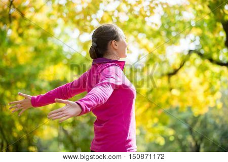 Portrait of an attractive smiling woman outdoors in a sportswear, her hands outstreched. Indian summer. Concept photo, side view