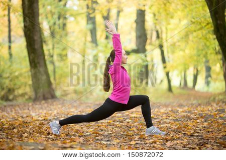 Sporty beautiful smiling young woman practicing yoga, standing in Warrior I posture, Virabhadrasana One pose, working out outdoors on autumn day wearing sportswear sweatshirt. Full length, side view