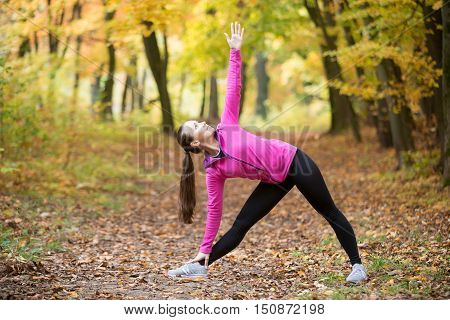 Sporty beautiful young woman practicing yoga, standing in Utthita Trikonasana posture, Extended Triangle pose, working out outdoors on autumn day wearing sportswear sweatshirt. Full length, side view
