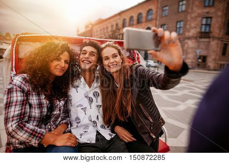 Teenage friends taking selfie on tricycle. Young man and women riding on tricycle bike and taking self portrait.