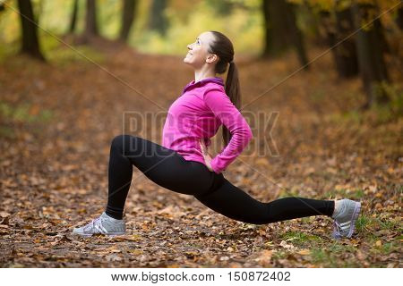 Sporty beautiful happy young woman practicing yoga, standing in low lunge exercise, anjaneyasana, ashwa sanchalanasana, working out outdoor on autumn day wearing sportswear sweatshirt. Full length
