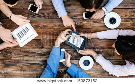 Top View of Business Team Young People Hands holding Electronic Gadgets with Professional Charts discussing and interacting