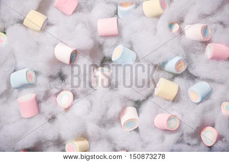 Top view of pastel colored marshmallow on a cotton background. Minimalism style.