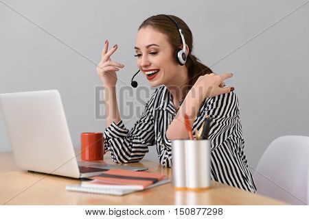 Skillful call operator is speaking into microphone and laughing. She is sitting at desk and looking at laptop with joy. Woman is wearing headset