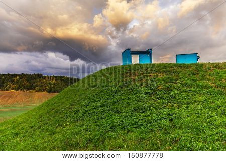 Grassed hill with two objects and dense clouds illuminated. Moravian landscape Svitavka.