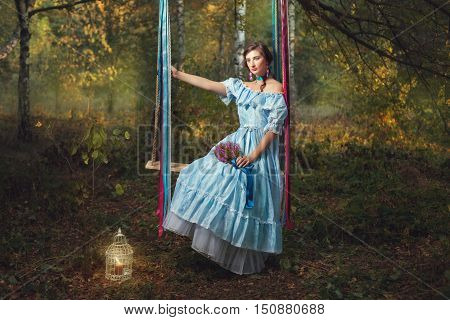 Sad woman sitting on a swing and holding a bouquet of wildflowers.