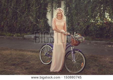 Modest girl in the pink dress is walking in a park on a bike.