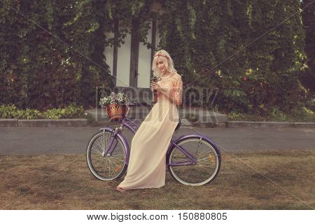Modest girl in the pink dress is walking in a park in the hands holding a bouquet of flowers she by bike.