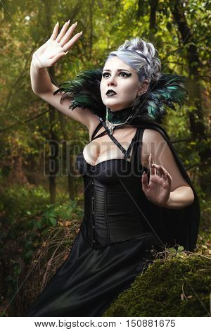 Gothic girl in black dress looking up.