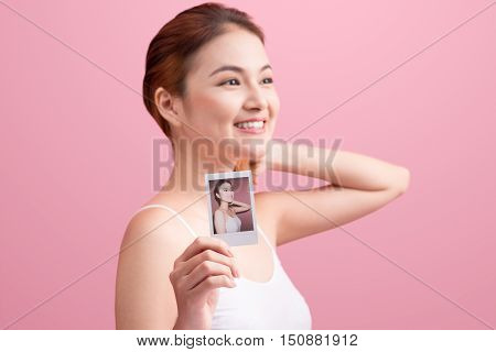 Young asian woman holding her picture on pink background.