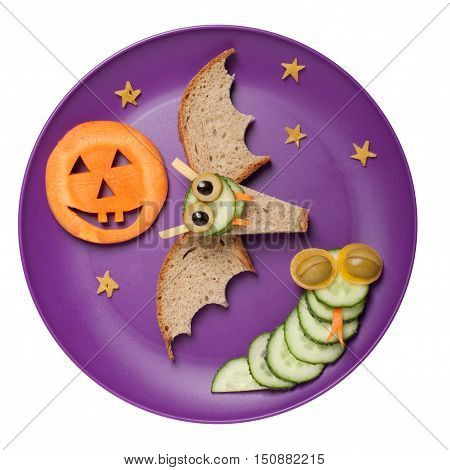 Halloween bat and snake made of bread and cucumber on plate