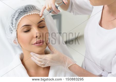 Serene young woman is getting botox injection into her forehead. She is sitting in doctor office and relaxing