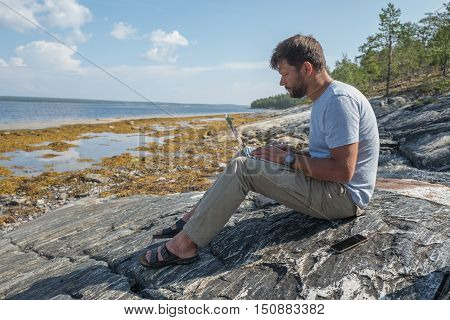 Handsome man is seating on the stone near of the sea and working with laptop