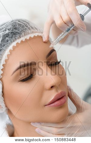 Close up of surgeon arms injecting female forehead with botox. Young woman closed eyes with serenity