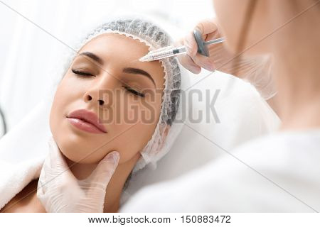 Professional beautician is making botox injection into female forehead. Calm young woman is lying with closed eyes
