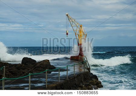 Storm ocean waves hitting old boat crane