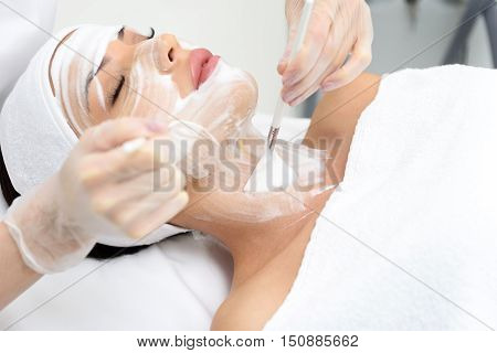 Healthy young woman is enjoying skin care treatment at beauty salon. She is lying and resting with pleasure. Hands in gloves applying cream on her neck by brush