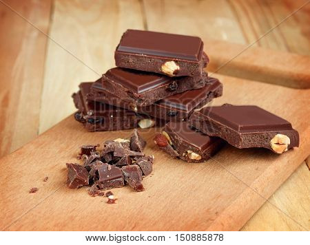 Pieces of chocolate and chocolate chips close-up. It is loved by all. Sweet Tooth. Cooking. Bakery products. Christmas baking ingredients. Aromas holiday. Home comfort.