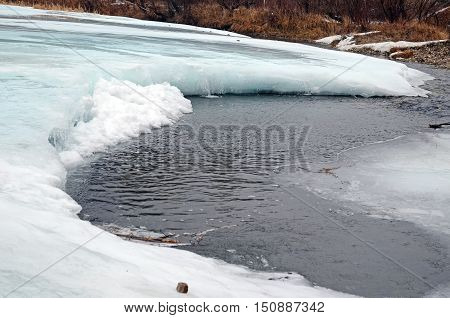 Icebound river on a cloudy spring day. Irkutsk Region, Russia