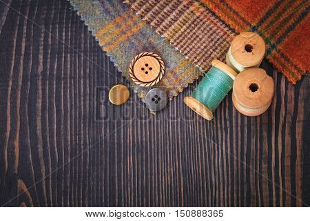 Thimble buttons spools of thread and fabric swatches on a wooden background close up
