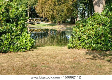 Painted metal footbridge over a small river in a Dutch nature area. It's a sunny day in the autumn season at a park
