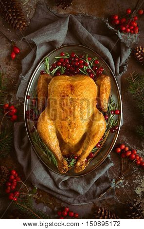 Christmas traditional dish roasted chicken in an oval dish decorated in a rustic style according to season dark moody stylized photo view from above
