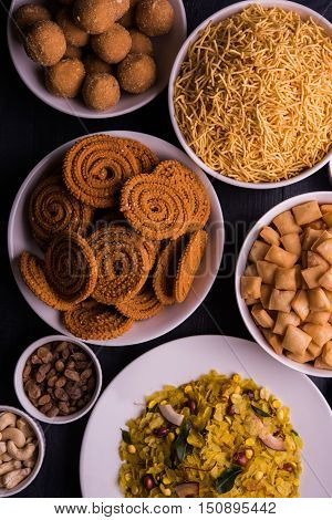 homemade tasty Diwali food or Diwali snacks or Diwali sweets like rava laddu, chakli, sev, shankar pale and chivda or chiwada with dry fruits in white bowls, favourite indian diwali recipe