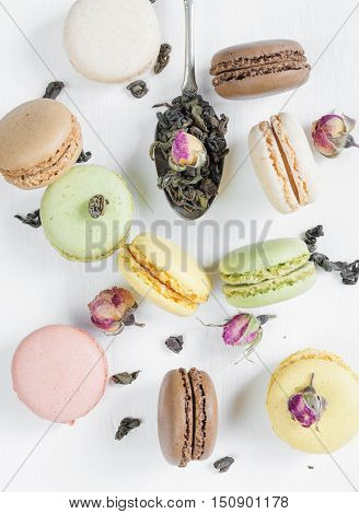 Multicoloured macaroons tea dried rose buds and teaspoon on white background; top view flat lay