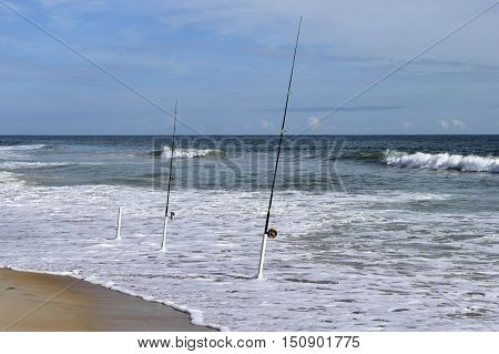 Surf fishing poles on the beach nobody there