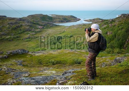 tourist with a camera on the coast of the Barents Sea