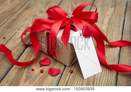 Valentines Day gift and small hearts with greting cart on a wooden background