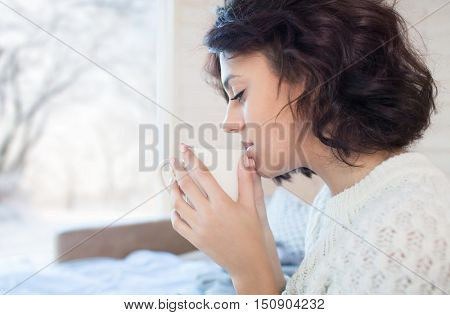 Young beautiful brunette woman drinking cup of coffee sitting home by the window. Winter snow landscape view. Lazy day off concept