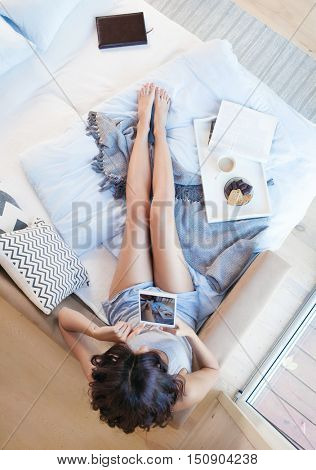 Young beautiful brunette woman with tablet computer taking selfie sitting down on the bed by the window. Top view from above. Lazy day off concept