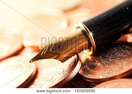 Beautiful fountain pen closeup and coins.Photo closeup Pen